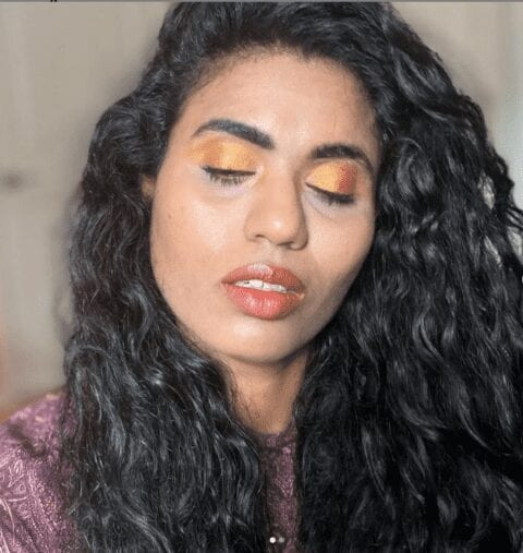 portrait of medium skin tone woman, with her eyes closed, showing off her golden eye makeup on her eyelids