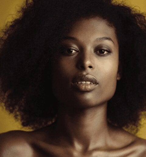 portrait of a black woman with a mustard coloured backdrop