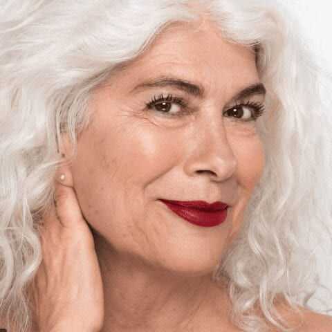 Portrait of light skinned woman with red lipstick and white grey hair. She is softly smiling