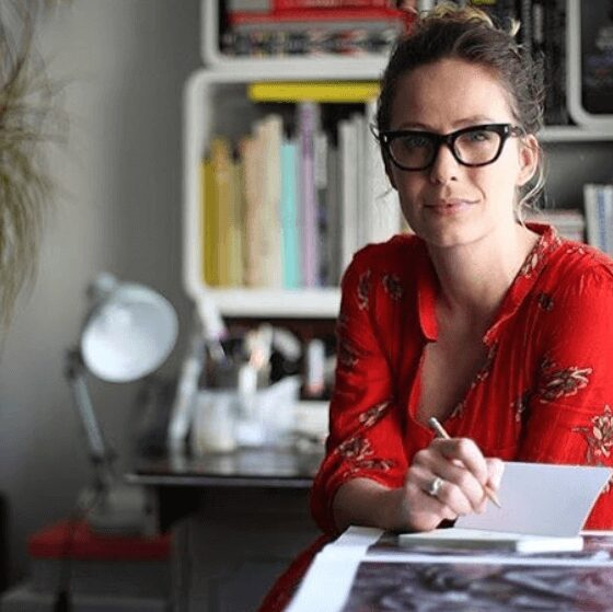 Khandiz, wearing a red dress and glasses looking into camera. There is book on the table and she is holding a pen as she invites you to learn more about khandiz