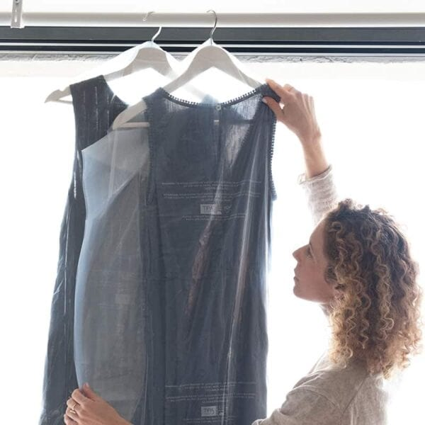 Woman holding up clothing covered in a Simply Stem TIPA Garment Bag